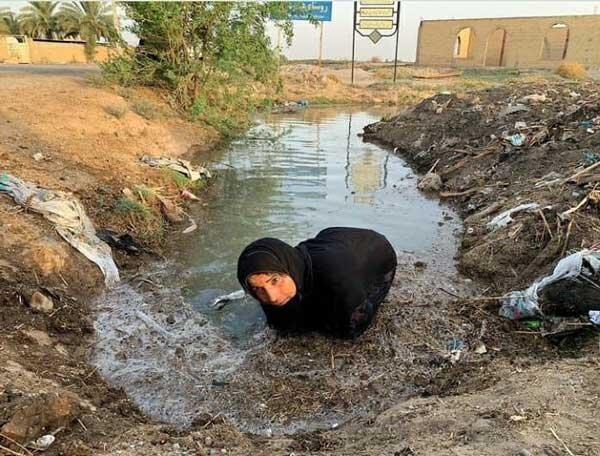 زن خوزستانی در حال تلاش برای باز کردن راه آب
