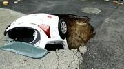 سقوط خودرو به داخل گودال بزرگ وسط خیابان / فیلم